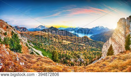 Awesome Autumn In Dolomite Alps With Larches I And Mountaines Marmolada And Monte Civetta At Sunset.