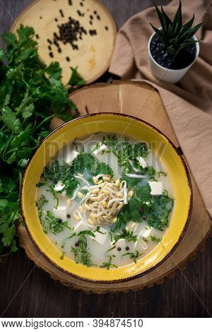 Cold Soup Broth In A Deep Yellow Bowl With Bean Sprouts, Shredded Herbs, Feta Chunks, Black Pepperco