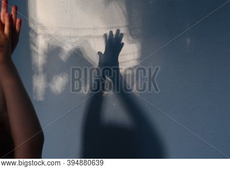 Child Claps Hands On Unfocused Foreground And Focus To Blurry Hand Shadows On Wall Background. Game