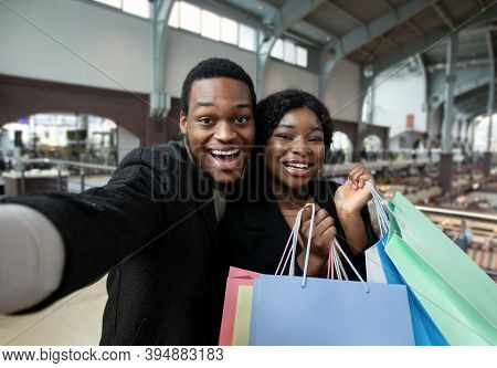 Amorous Dates With Shopping Bags In Modern City Mall. Portrait Of Young Smiling African American Mal
