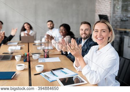 Successful Business People Applauding Celebrating Success Smiling To Camera Sitting At Desk At Corpo