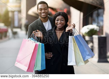 Season Sale, Consumerism, Black Friday And Family Walk. Smiling Young African American Couple Hugs,