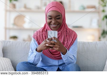 Young Black Muslim Woman In Hijab Browsing Social Networks On Smartphone While Relaxing At Home, Afr