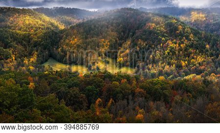 Small Farm In The Center Of A Colorful Forest In Rural Tennessee Under Ominous Skies