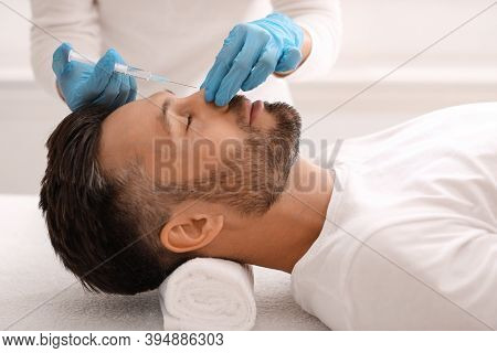 Unrecognizable Plastic Surgeon In Protective Gloves Making Nonsurgical Rhinoplasty For Handsome Man