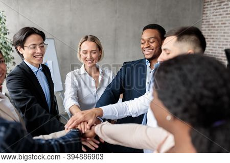 Teamwork And Teambuilding. United Business Team Holding Hands Standing In Circle In Modern Office. D