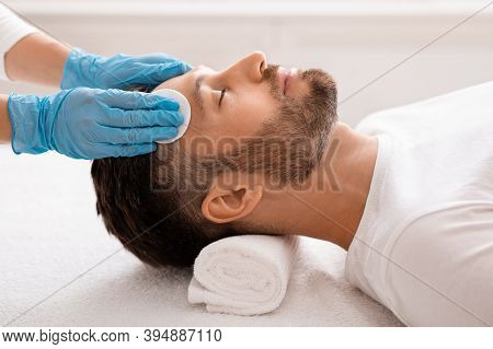 Middle Aged Handsome Man Attending Cosmetologist, Male Face Care Concept. Side View Of Unrecognizabl
