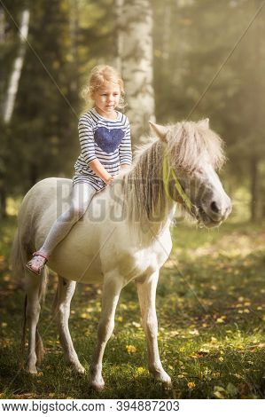 Little Blond Girl Riding Little Horse Pony In Summer Forest