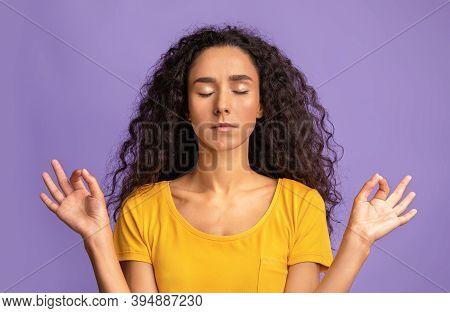 Zen. Calm Brunette Lady Meditating Over Purple Studio Background, Keeping Hands In Mudra Gesture, Re