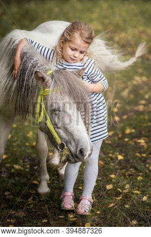 Little Blond Girl Is Standing Near The Little Horse Pony And Hugging It In Summer Forest
