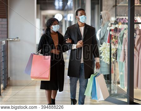 Couple Walking Past Shop Window And Looking In. Millennial African American Male And Female In Prote