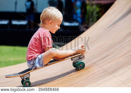 Funny Skateboard Riding. Little Child With Surf Skateboard Have Fun In Beach Skate Park. Active Fami