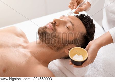 Relaxed Man Attending Cosmetologist Or Spa Salon, Enjoying Weekend. Bearded Middle Aged Man Getting
