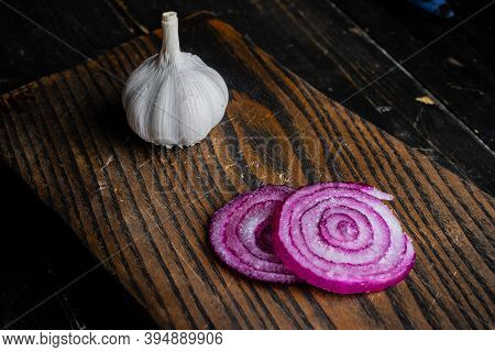 Onion, Garlic And Salt On A Wooden Cutting Board. Top View.