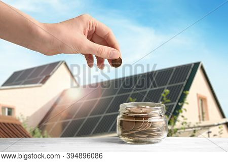 Woman Putting Coin Into Jar Against House With Installed Solar Panels On Roof, Closeup. Economic Ben
