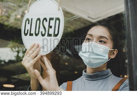 Reopen. Friendly Waitress Wearing Protection Face Mask Turning Closed Sign Board On Glass Door In Mo