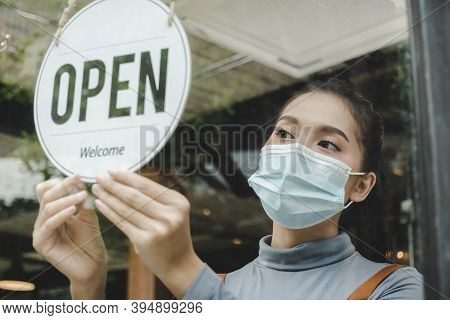 Reopen. Friendly Waitress Wearing Protection Face Mask Turning Open Sign Board On Glass Door In Mode