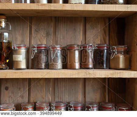 Bottles With Spices And Seasonings In Wooden Rack. Various Different Organic Herbs For In The Kitche