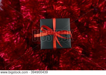 Christmas Black Gifts Box On Red Tinsel Background, Abundant Decor