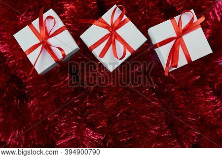 Christmas White Gifts Box On Red Tinsel Background, Abundant Decor