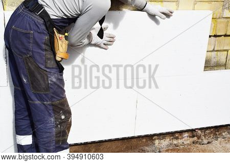 Worker Installing White Rigid Polyurethane Foam Sheet On Building Wall Facade For Energy Saving. Diy