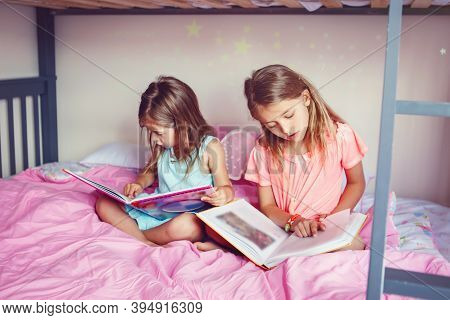 Happy Caucasian Sisters Girls Reading Books In Bedroom. Children Siblings At Home Spending Time Toge