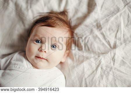 Closeup Portrait Of Cute Caucasian Red-haired Newborn Baby. Adorable Funny Child Infant With Blue Gr