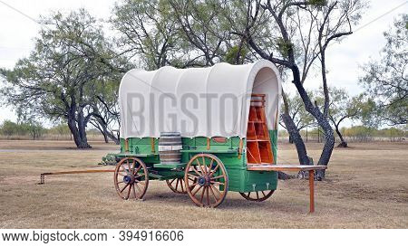 Old Wild West Covered Wagen In Texas With Mesquite Trees In Background.