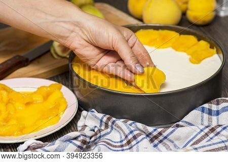 Cooking Cheesecake. The Cook Decorates The Cheesecake With Sliced Fruit. Woman Decorates Cheesecake.