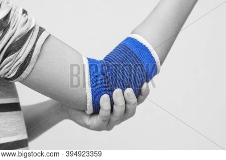 Elbow Wrapped In Elastic Bandage, Elbow Pain. A Child With A Therapeutic Elastic Band On His Elbow