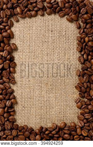 Vertical frame made from black coffee beans on rustic burlap fabric background.