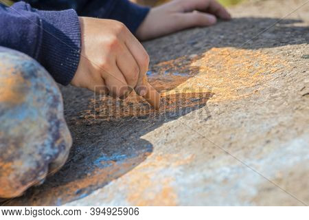 The Child Drawing A Chalk On Asphalt. Child Drawings Paintings On Asphalt Concept. Kid Is Playing Wi