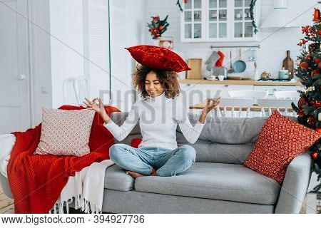 Kinky Haired Lady With Dark Skin Wearing White Sweater Holding Red Pillow On Head Sits In Lotus Yoga