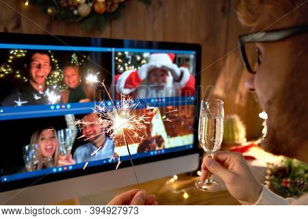 Young Man Wears Christmas Hat Drinking Champagne Holding Sparkler Talking To Friends On Virtual Vide