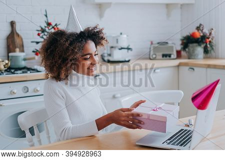 Smiling African Lady With Kinky Hair Holds Decorated Present Box Near Notebook Monitor Sitting At Mo