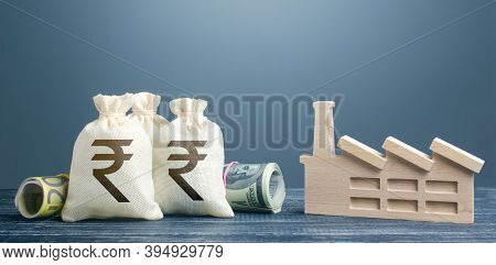 Indian Rupee Money Bags And Industrial Factory Plant. Investments In Production And Energy Industry.