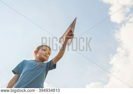 Little Boy Launches A Paper Plane Into The Air. Child Launches A Paper Plane. Happy Kid Playing With