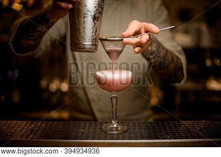 Male Bartender Filters Whipped Cocktail Through Sieve Into Wine Glass On Bar Counter