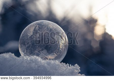 Frozen Soap Bubble With A Beautiful Pattern On The Snow Close-up On A Blurry Blue Background.  Selec