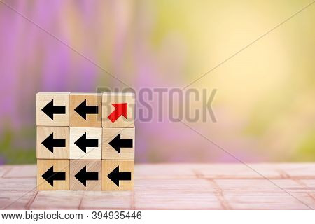 Wood Block Red Arrow Pointing The Opposite Way Disruptive From The Black Arrows On Table Wooden.uniq