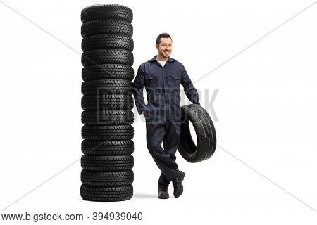 Full length portrait of an auto mechanic holding a tire leaning on a pile of car tires  isolated on white background