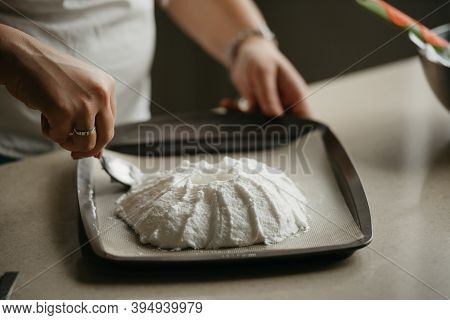 А Close Photo Of The Hands Of A Young Woman Who Is Creating With A Spoon A Shape Of A Big Meringue O