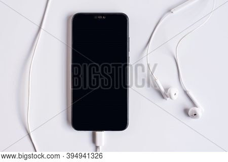 Smartphone With Earphones On White Background. Close-up Of Smart Phone With Headphones On A White Ba