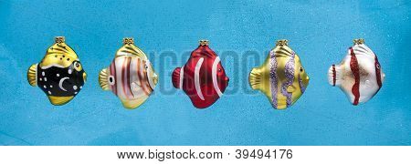 Colorful fish Christmas ornaments on blue
