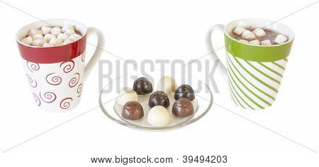 Colorful ceramic mugs with hot chocolate, marshmallows and chocolate candy on white