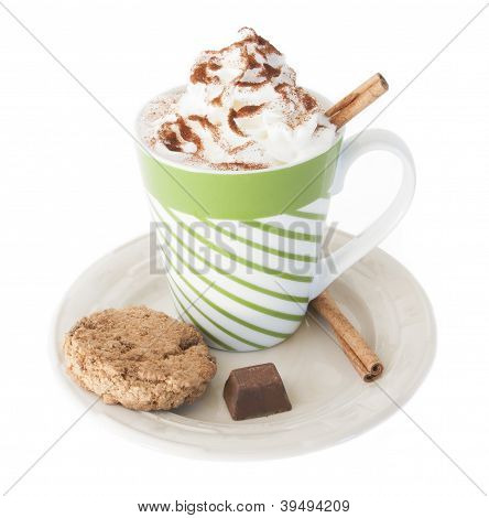 Cup of hot chocolate, whipped cream, cinnamon, a cookie candy on white