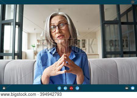 Senior Mature Old Woman Online Teacher, Remote Tutor, Distance Coach Talking To Web Cam Virtual Coun