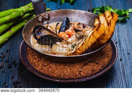 Mixed Seafood Saute Served With Toasted Bread In A Pan