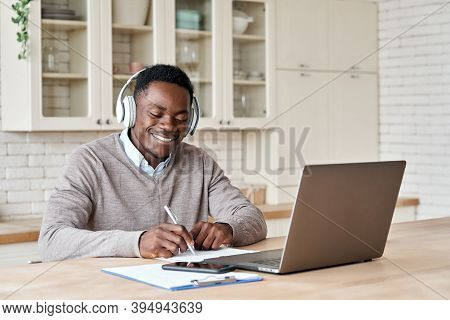 Happy African Business Man, Black Male Student Wearing Headphones Elearning On Laptop Computer Sitti