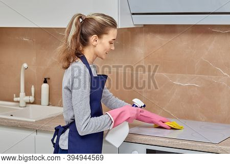 Beautiful Woman Cleans The Kitchen, Washes The Electric Stove With Detergent.